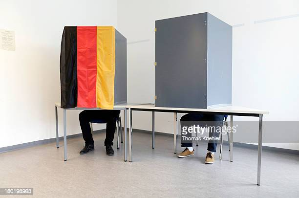 In this photo illustration two voters in their polling booths one covered with the German national flag at the the local polling station in...