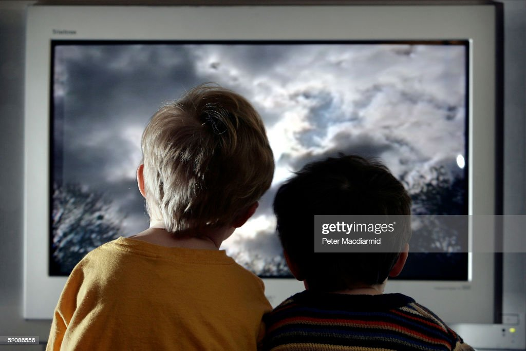 In this photo illustration two young child watch television at home, January 27, 2005 in London, England.