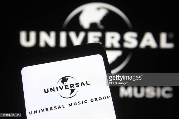 In this photo illustration, Universal Music Group logo is seen on a smartphone and pc screen.