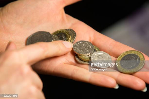 In this photo illustration various coins of the pound sterling are seen in a woman's hand