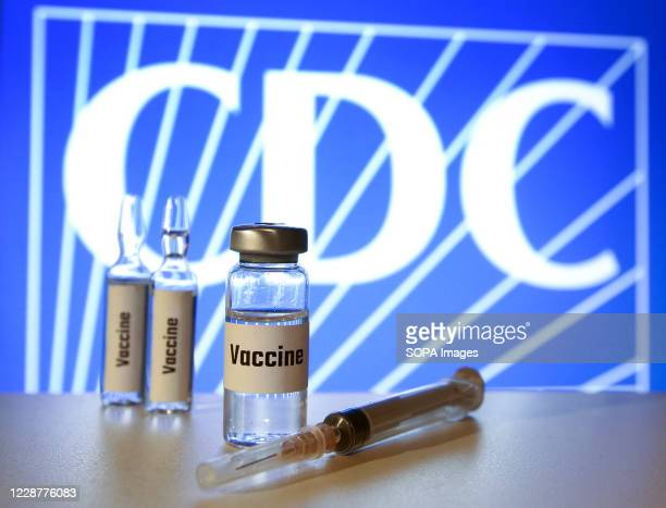 In this photo illustration, vials of fake 'Covid-19 Vaccine' and a syringe seen displayed with a logo of Centers for Disease Control and Prevention...