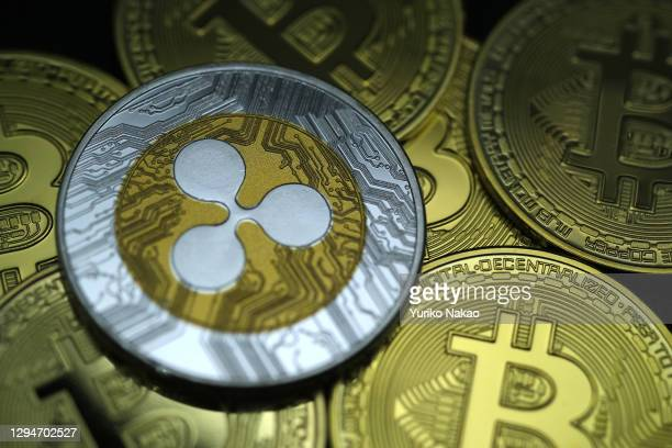 In this photo illustration, visual representations of digital cryptocurrency Ripple and Bitcoin are arranged on January 3, 2021 in Katwijk,...