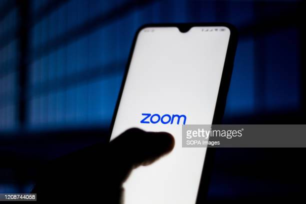 In this photo illustration Zoom Meetings logo is seen displayed on a smartphone.