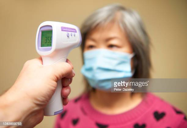 In this photo illustration,a patient having her temperature taken during an NHS Coronavirus test Photographed by Peter Dazeley, Kingston On Thames,...