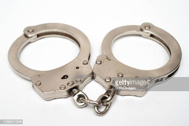 In this photo illustrations handcuffs are seen on display.