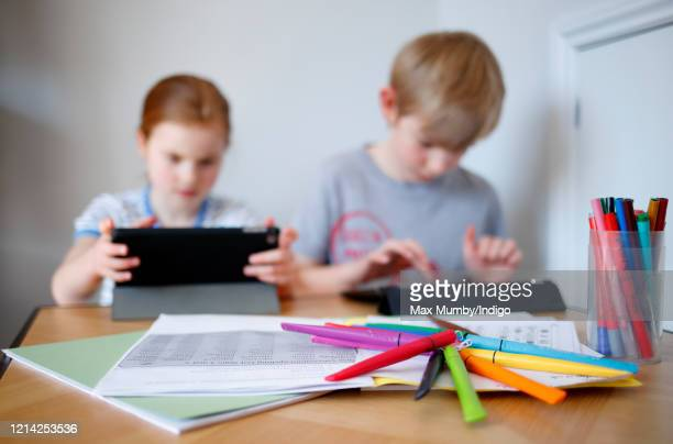 In this photo illustration,schoolchildren use iPads to complete online schoolwork at home whilst schools are closed due to the Coronavirus pandemic...
