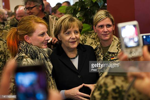 In this photo provided by German Government Press Office German Chancellor Angela Merkel is photographed with soldiers as she visits the German...