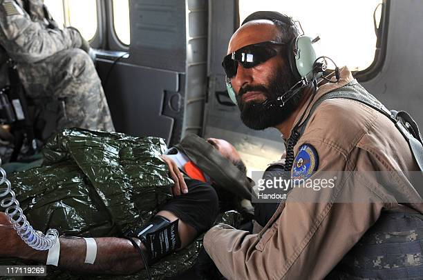 In this photo provided by ISAF Regional Command Afghan Air Force flight medic Sgt Gulap Ahmadzia monitors the blood pressure and pulse of an Afghan...