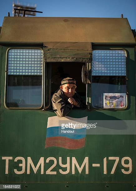 In this photo provided by NASA A railroad engineer looks out from the locomotive that is used to deliver the Soyuz rocket to the launch pad on...
