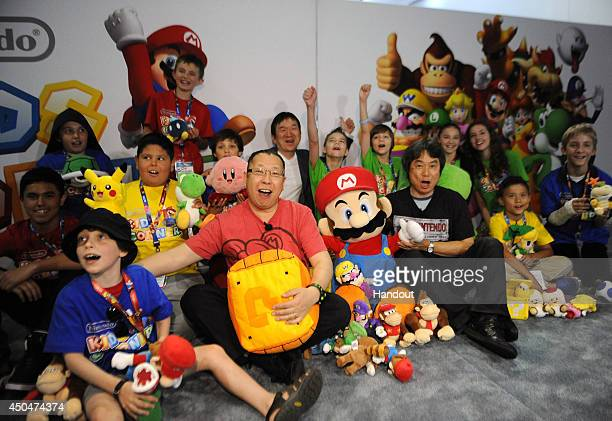 In this photo provided by Nintendo of America a select group of kids enjoy meeting video game luminaries Shigeru Miyamoto the creator of Super Mario...