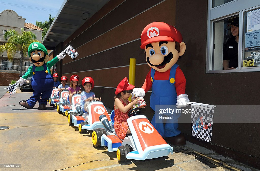 In this photo provided by Nintendo of America, Mario and Luigi direct children ride through the McDonald's drive-thru in Mario Kart Ride On vehicles on July 12, 2014 in Los Angeles, California. Nintendo is celebrating the recently released Mario Kart 8 game for the Wii U console by partnering with McDonald's nationwide to include themed toys in Happy Meals.