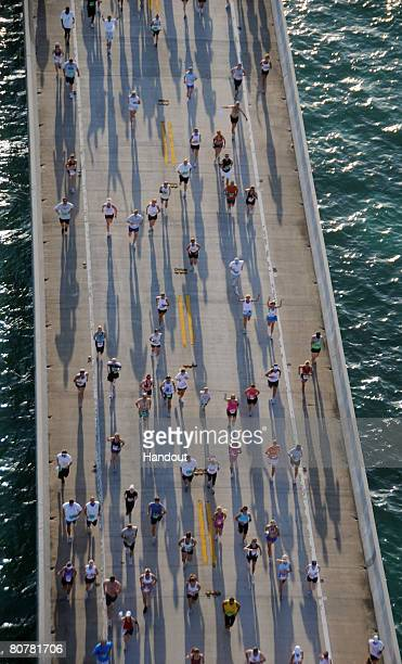 In this photo provided by the Florida Keys News Bureau, Competitors in the Seven Mile Bridge Run in the Florida Keys cast early morning shadows on...