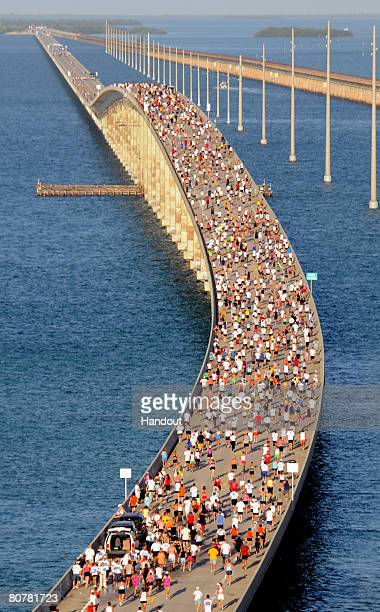 In this photo provided by the Florida Keys News Bureau, Competitors in the Seven Mile Bridge Run in the Florida Keys traverse over the highest point...