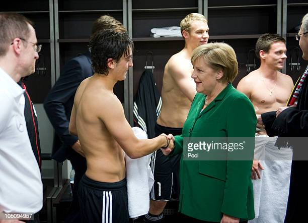 In this photo provided by the German Government Press Office German Chancellor Angela Merkel congratulates German national player Mesut Oezil next to...