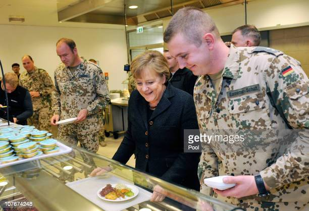 In this photo provided by the German Government Press Office German Chancellor Angela Merkel eats together with soldiers in the canteen during her...