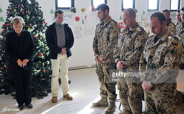 In this photo provided by the German Government Press Office German Chancellor Angela Merkel and Defense Minister KarlTheodor zu Guttenberg hold a...