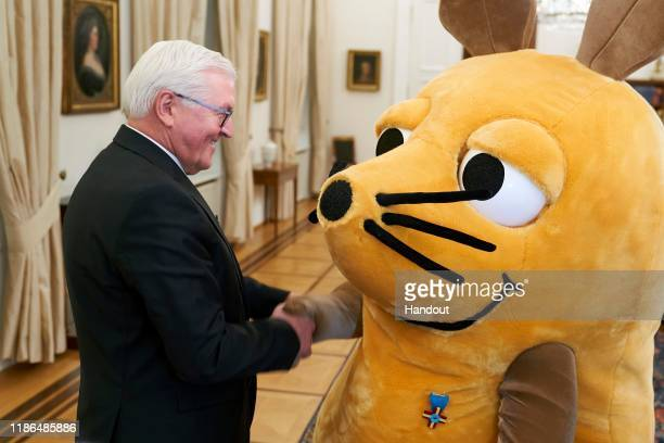 "In this photo provided by the German Government Press Office , German President Frank-Walter Steinmeier decorates ""die Maus"" with a medal in Bellevue..."
