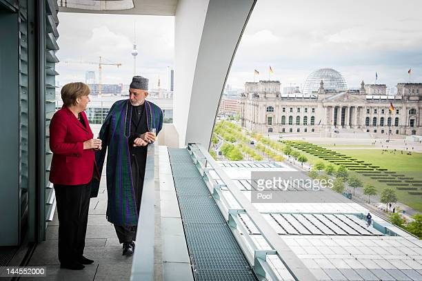 In this photo provided by the German Government Press Office German Chancellor Angela Merkel talks with Afghan President Hamid Karzai as they take in...