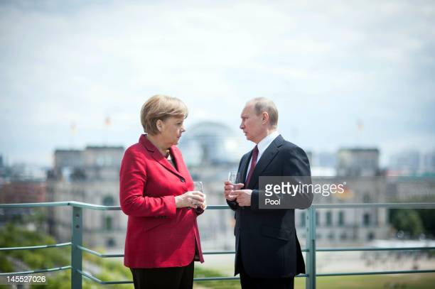 In this photo provided by the German Government Press Office German Chancellor Angela Merkel welcomes Russia's President Vladimir Putin with military...