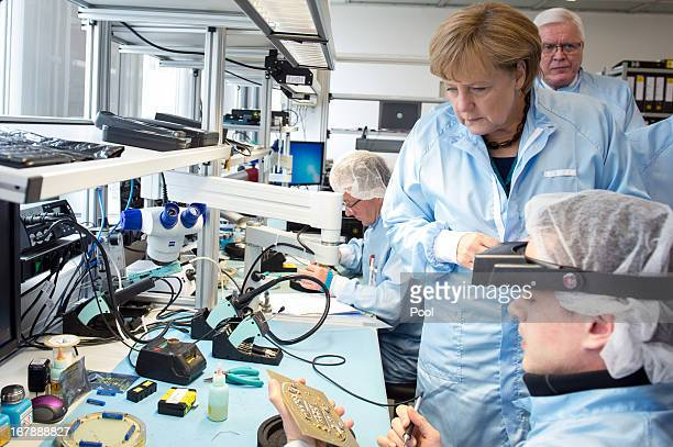 In this photo provided by the German Government Press Office German Chancellor Angela Merkel wears overalls as she visits JenaOptronik GmbH factory...
