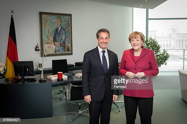 In this photo provided by the German Government Press Office German Chancellor Angela Merkel and former French President Nicolas Sarkozy meet at the...