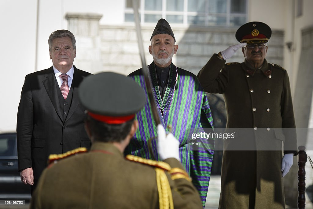 In this photo provided by the German Government Press Office (BPA), Afghanistan President Hamid Karzai (C) and German President Joachim Gauck review a guard of honour at the Presidential Palace on December 18, 2012 in Kabul, Afghanistan. The visit is Gauck's first to the region since taking office.