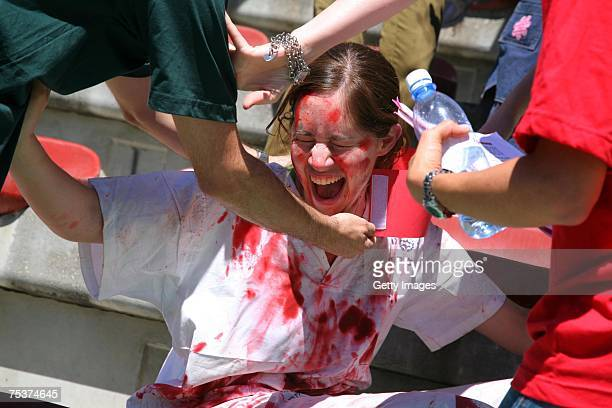 In this photo provided by the Hadassah School of Medicine, a medical student feigns pain as she is treated during a civil defense exercise held at a...