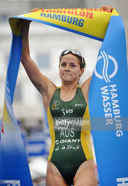 In this photo provided by the International Triathlon Union Australia's Erin Densham victoriously raises the finish tape to win the Dextro Energy...
