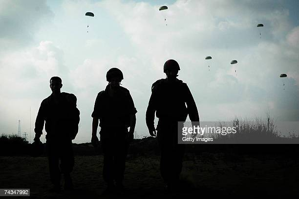 In this photo provided by the Israeli Defense Forces , army paratroopers carriy their battle gear after completing a training jump May 28, 2007 over...