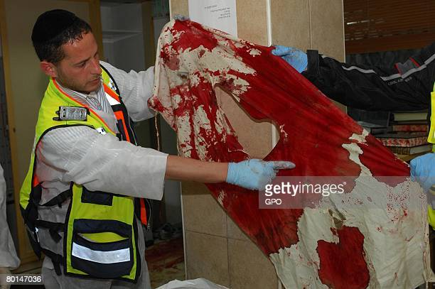 In this photo provided by the Israeli Government Press Office a volunteer from the ultraOrthodox Zaka rescue organization points out a bullet hole in...