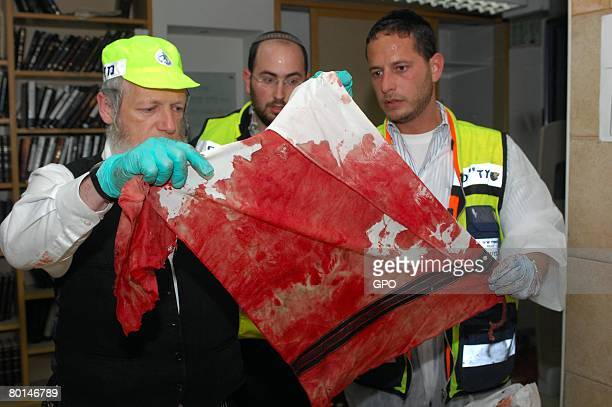 In this photo provided by the Israeli Government Press Office volunteers from the ultraOrthodox Zaka rescue organization hold up a victim's bloody...