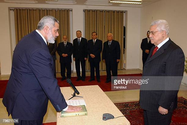 In this photo provided by the Palestinian Press Office Palestinian Authority Prime Minister Ismail Haniyeh of Hamas places his hand on the Quran...