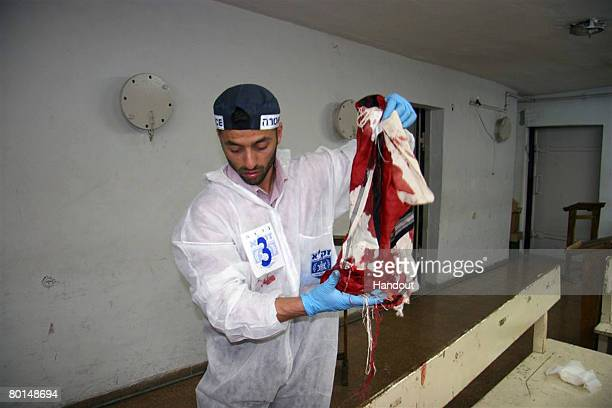 In this photo provided by the ultraOrthodox ZAKA Jewish rescue organization a ZAKA volunteer collects a victim's bloody prayer shawl in the library...