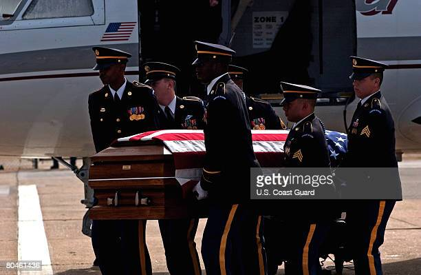 In this photo provided by the US Coast Guard on April 1 the Army Honor Guard removes the casket of Army Sgt Gregory D Unruh from a military plane at...