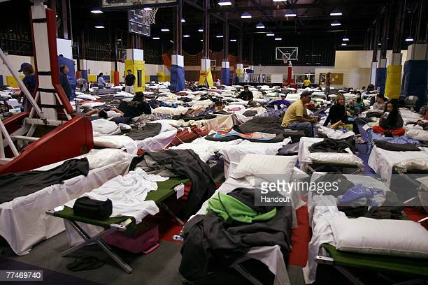 In this photo provided by the US Navy Evacuees from San Diego County take refuge in the Sports Warehouse Gym on board Naval Air Station North Island...
