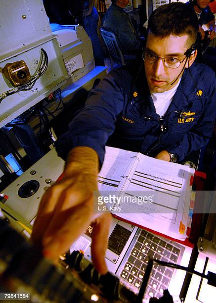 In this photo provided by the U.S. Navy, Lt. Cmdr. Andrew Bates operates the radar system control in the combat information center during a ballistic...