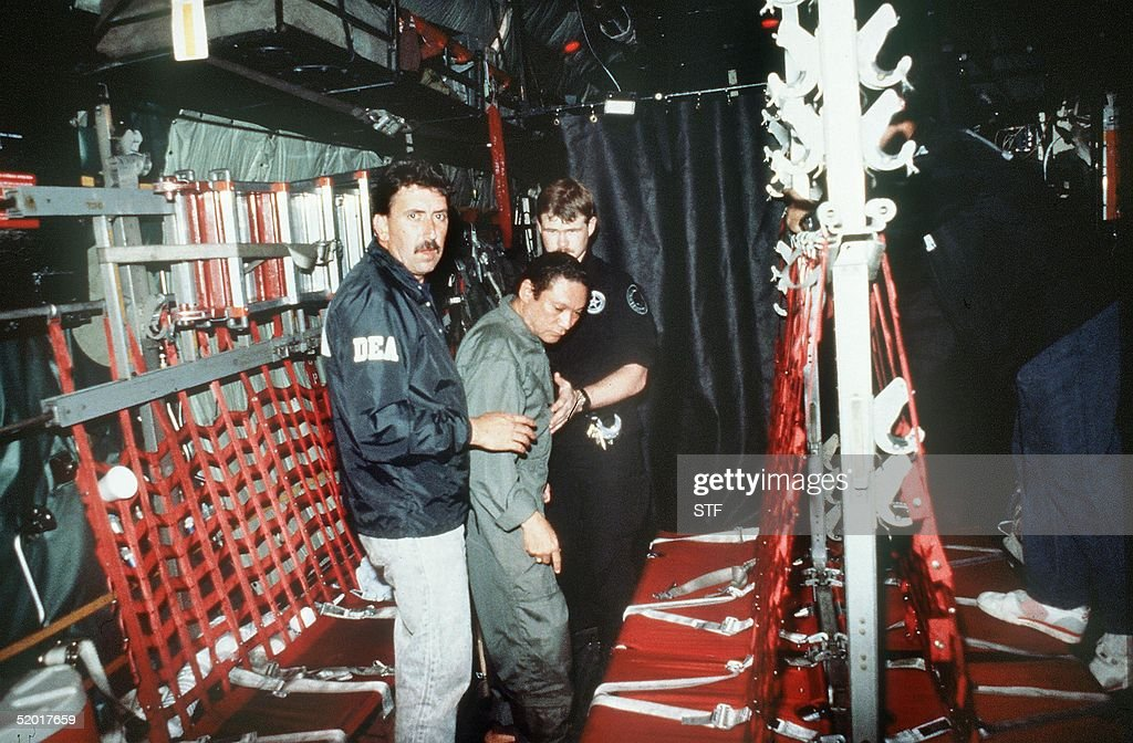 In this photo released 04 January 1990 by the Defense Department, Panamian General Manuel Noriega (C) is brought on board a US military plane 3 January 1990 for a flight to Miami after his arrest.