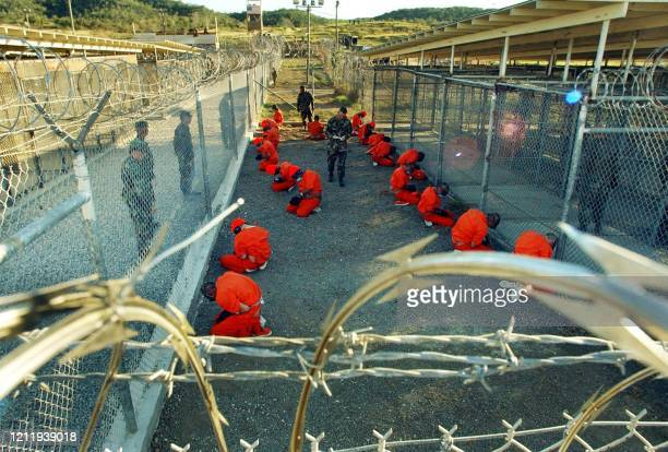 In this photo released 18 January 2002 by the Department of Defense, Al-Qaeda and Taliban detainees in orange jumpsuits sit in a holding area under...