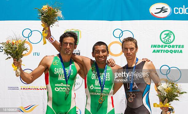 In this photo released by the International Triathlon Union, Crisanto Grajales and Sergio Sarmiento of Mexico, and Manuel Huerta of the USA stand...