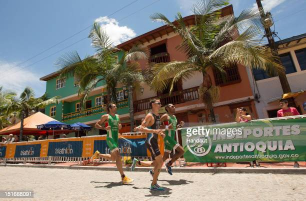 In this photo released by the International Triathlon Union, Crisanto Grajales of Mexico runs with teammate Sergio Sarmiento, and Manuel Huerta of...