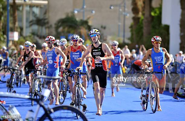 In this photo released by the International Triathlon Union Switzerland's Sven Riederer and Spain's Javier Gomez run into the second transition at...