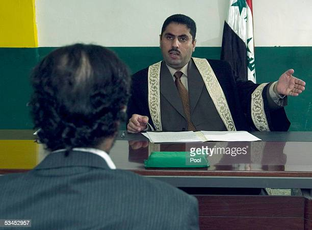 In this photo released by the Iraqi Special Tribunal Chief Investigative Judge Ra'id Juhi questions Saddam Hussein August 23 2005 in Iraq Hussein...