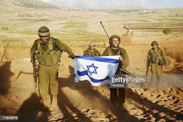 In this photo released by the Israel Defense Forces Israeli infantry troops proudly carry their national flag as they return after fighting Hezbollah...