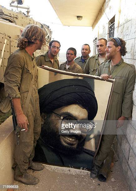In this photo released by the Israel Defense Forces Israeli soldiers pose with a large portrait of Hezbollah leader Sheikh Hassan Nasrallah in a...