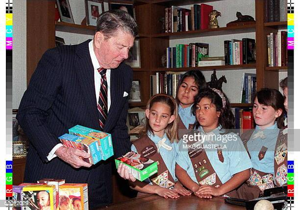 In this photo released by the Reagan Library 06 February Former US President Ronald Reagan receives cookies from members of Girl Scout Troop as a...