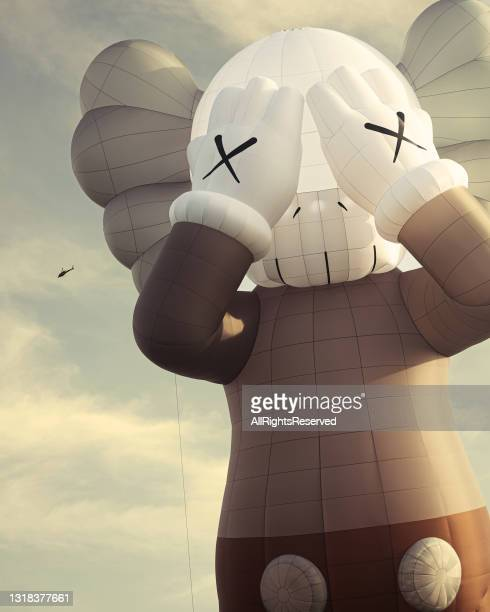 In this photo released on May 17 Artist KAW's latest work and the 42-meter tall hot-air balloon 'KAWS:HOLIDAY' takes flight prior to May 16, 2021 in...