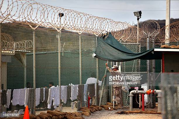 In this photo reviewed by the US Military a guard leans on a fence talking to a Guantanamo detainee inside the open yard at Camp 4 detention center...