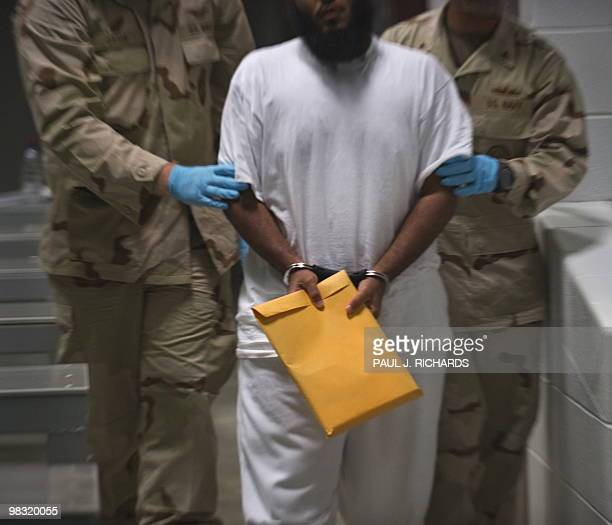 In this photo reviewed by US military officials US military guards at Campt VI move a detainee back to his cell after he attended a lifeskills class...