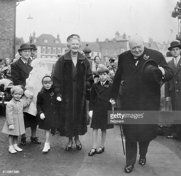 In this photo Sir Winston Churchill and Lady Churchill are shown arriving at Westerham Parish London for the christening of their ninth grandchild...