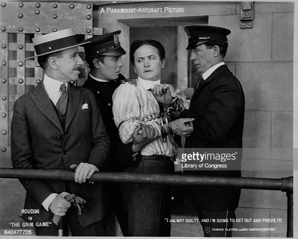 In this photo still from the movieThe Grim Game Houdini with hands shackled and held firmly by two guards looks back at the warden and Vows I am not...